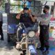 CEGAH: anggota Polsek saat memasangkan masker pada pendendara