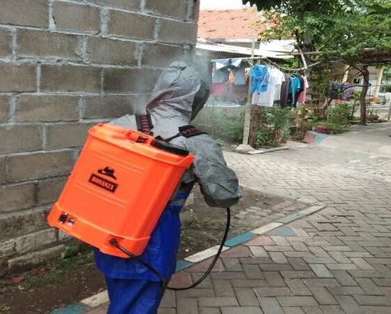 Petugas penyemprot disinfektan saat melaksanakan tugas.